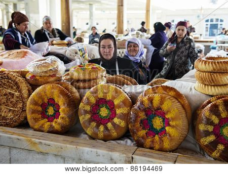 SAMARQUAND, UZBEKISTAN - MARCH 14, 2015: City grocery market.  Women sell traditional Uzbek bread.