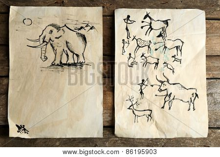 Rock paintings on paper on wooden background