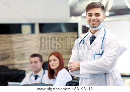 Attractive male doctor with team in conference room
