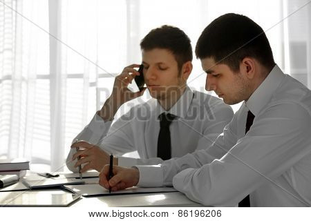 Two handsome businessmen working in office