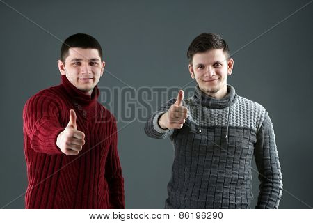 Two handsome young men on gray background