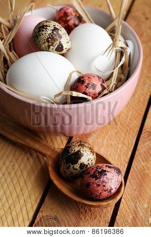 Bird colorful eggs in bowl on wooden background