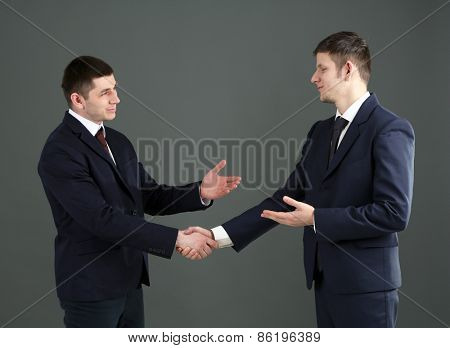 Two handsome businessmen on gray background