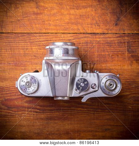 Vintage photo camera on a wooden background, top view