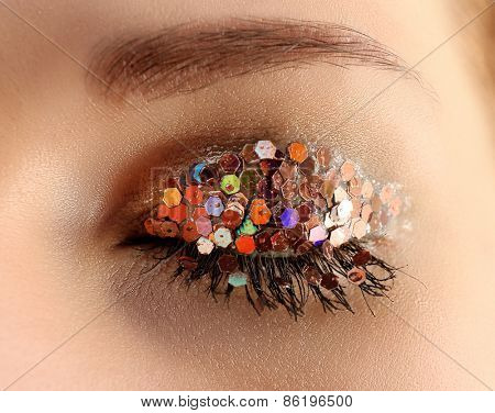 Female eye with fancy glitter makeup, macro view