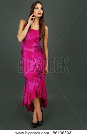 Beautiful young woman in long pink dress on dark gray background