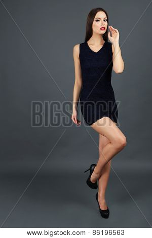 Beautiful young woman in short black dress on dark gray background