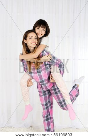 Two girls in pajamas on light background