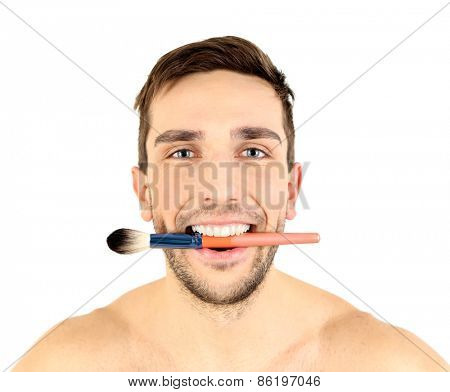 Handsome young man holding brush in his mouth isolated on white