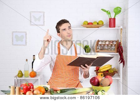 Man with recipe book in hands at table with different products and utensil in kitchen on white wall background