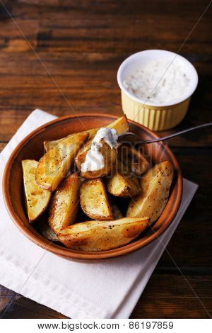Baked potatoes in bowl and sauce on table close up
