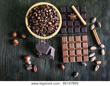 Still life with set of chocolate, spices and coffee grains on wooden table, top view