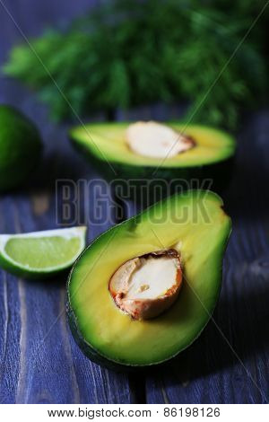 Sliced avocado with lime and herb on wooden table, closeup