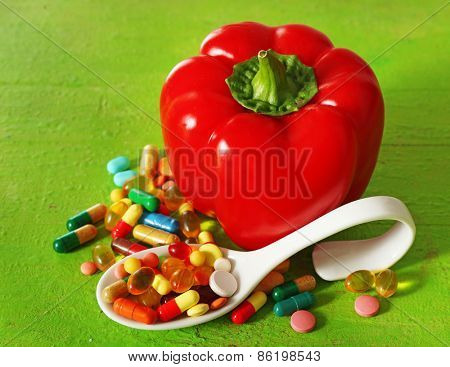 Paprika and colorful pills, on wooden background