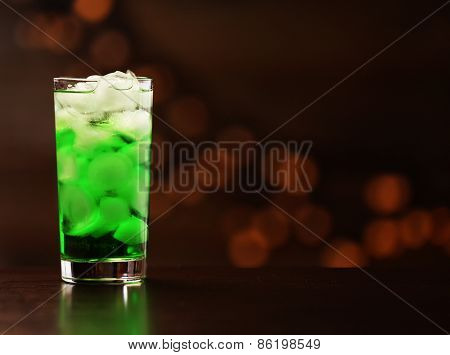 Green cocktail on table on brown background