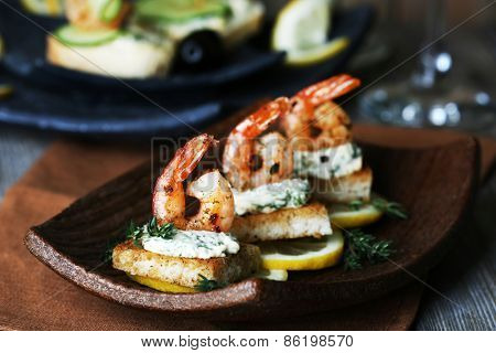 Appetizer canape with shrimp and lemon on plate on table close up