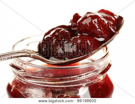 Jar of strawberry jam with spoon isolated on white