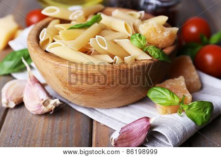 Raw pasta in bowl with cheese and vegetables on table close up