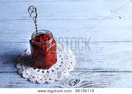 Jar of goji berry jam on lace doily on wooden background