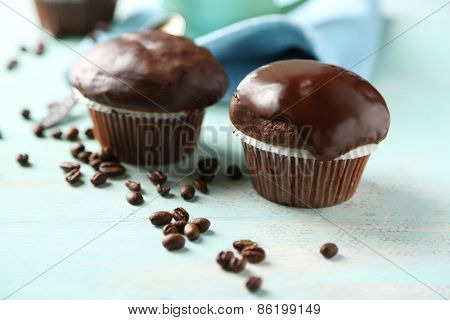 Tasty homemade chocolate muffins and cup of coffee on wooden table