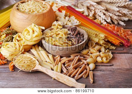 Different types of pasta on wooden table background