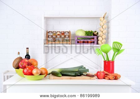 Table with different products in kitchen on white wall background