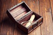 image of treasure chest  - old paper roll inside treasure chest on wooden background - JPG