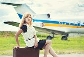 picture of old suitcase  - beautiful woman sitting on old suitcase against plane - JPG