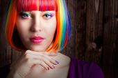 foto of wig  - beautiful woman wearing colorful wig and showing colorful nails against wooden background - JPG