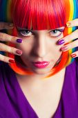 stock photo of wig  - beautiful woman wearing colorful wig and showing colorful nails against blue background - JPG