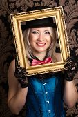 stock photo of cabaret  - beautiful cabaret woman posing with golden frame against retro wallpapers - JPG