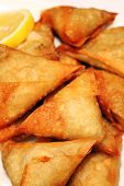 stock photo of samosa  - samosas with a lemon slice - JPG