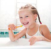 stock photo of human teeth  - Little girl brushing teeth in bath - JPG