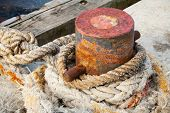 image of bollard  - Old rusted mooring bollard with naval ropes on concrete pier - JPG