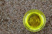 stock photo of flaxseeds  - A bowl of cold pressed Linseed yellow oil on flaxseed background - JPG