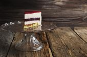 stock photo of cream puff  - piece of cake with a cream puff on a glass base on the old wooden background - JPG