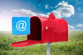 stock photo of postbox  - Red email postbox against sunny landscape - JPG