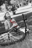 image of hurt  - Young female bicyclist with hurt leg sitting on grass in the park - JPG