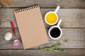 pic of vinegar  - Olive oil and vinegar with spices over wooden table background and notepad for copy space - JPG