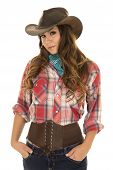 image of cowgirls  - A cowgirl with a small smile standing with her hands in her pockets - JPG