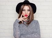 foto of nail paint  - beautiful sexy young girl in a black  hat with red full lips - JPG
