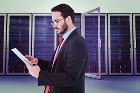 pic of scroll  - Businessman scrolling on his digital tablet against server towers - JPG