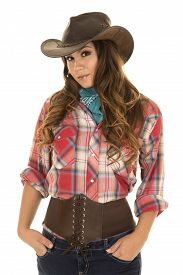 picture of cowgirl  - A cowgirl with a small smile standing with her hands in her pockets - JPG