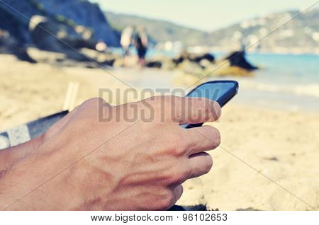 closeup of a young caucasian man using a smartphone on the beach