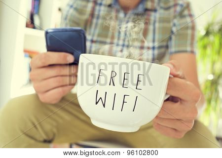 closeup of young caucasian man using a smartphone with a cup of coffee or tea with the text free wifi written in it