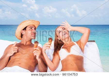 Happy couple relaxing on the beach resort, sitting on sunbed, eating tasty ice cream and with interest looking up in the sky, romantic honeymoon