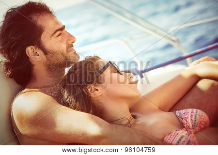 Peaceful couple relaxing on sailboat, lying down on the deck and enjoying tranquil summer trip on water transport, pleasure and enjoyment from romantic relationship