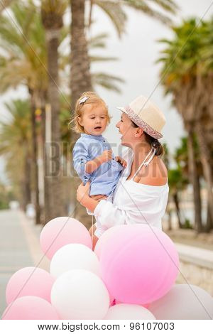 Trendy young mother with a baby daughter in her arms standing outdoors alongside a big bunch of pink and white party balloons on a tropical sidewalk,