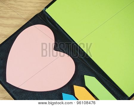 Sticky Paper With Pink Heart Shape, Arrow Shape On Black Notebook Wood Background