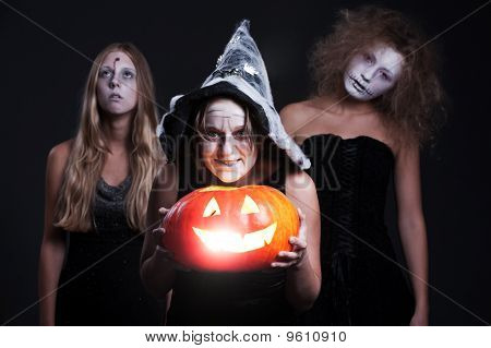 Three Halloween Personages With Orange Pumpkin
